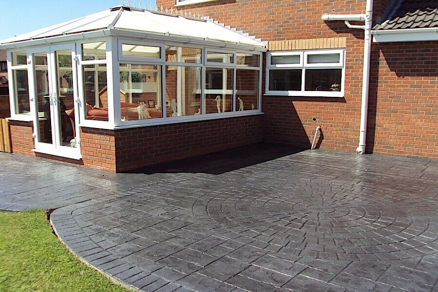 Conservatory with grey concrete patio outside