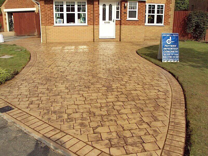 Tan-stone-pattern-imprinted-concrete-driveway