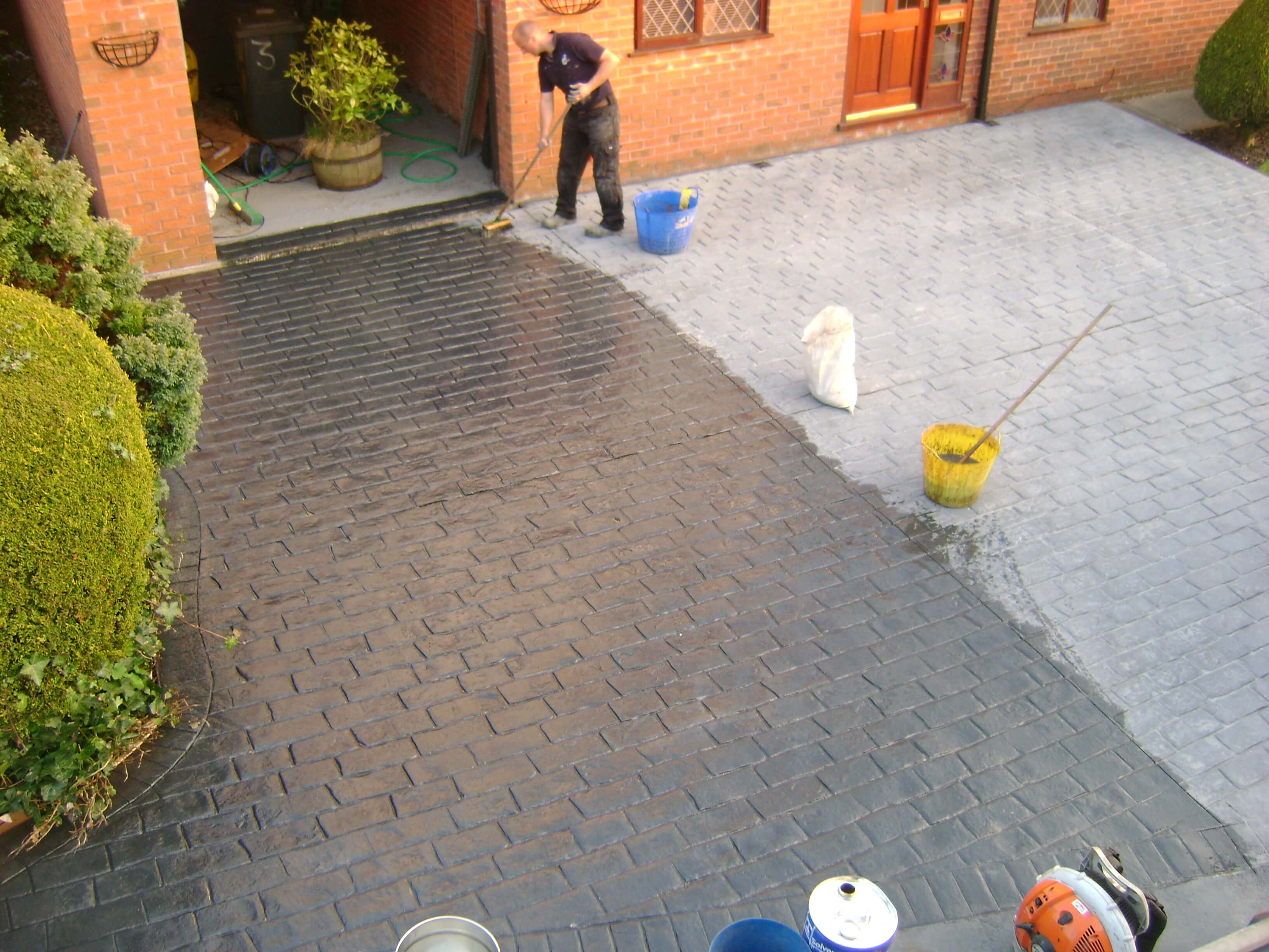 Applying sealant to concrete driveway